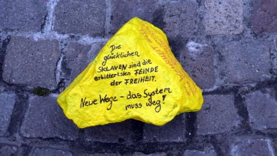 """Ein bemalter Stein u.a. mit dem Text """"neue Wege - das System muss weg!"""", welcher der Querdenker-Szene zuzuordnen ist."""